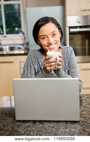 Happy brunette holding cup while using laptop in the kitchen