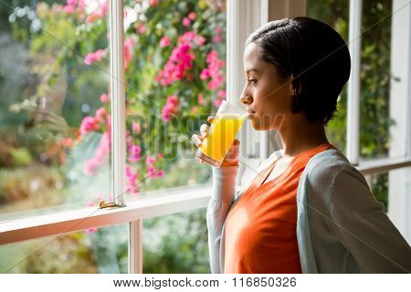 Thoughtful brunette drinking orange juice near the window