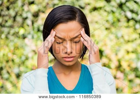 Portrait of frowning brunette with headache outdoors