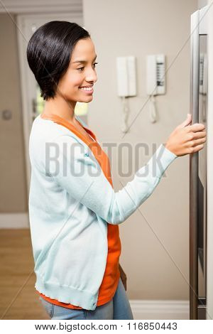 Smiling brunette with hand on refrigerator in the kitchen