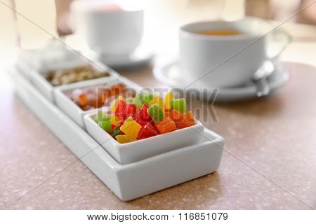 Set of candies and tea on table close up