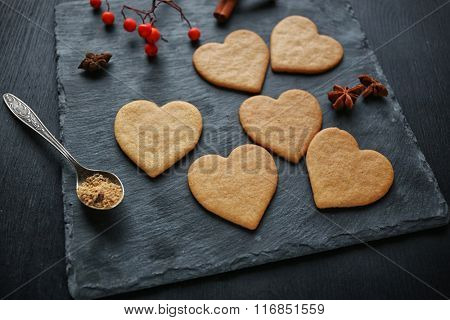 Heart shaped biscuits with ash berries on a mat