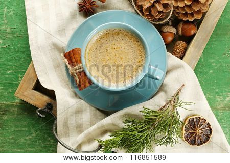 Cup of coffee on napkin on wooden tray, top view