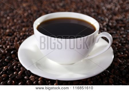 Cup of hot coffee on coffee beans background