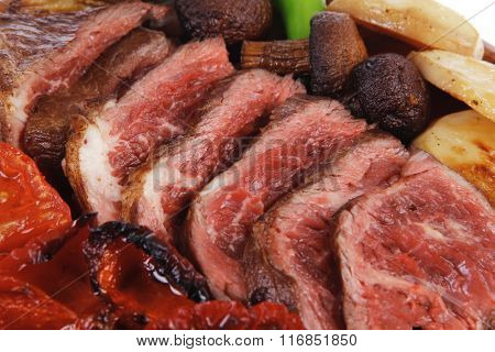fresh grilled bbq beef meat rib eye steak on wooden plate with baked tomatoes mushroom, potatoes, hot chili pepper isolated on white background