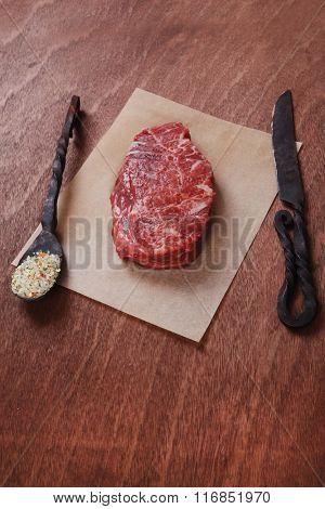 fresh raw beef rib eye steak on walnut table with salt spice and black iron antique forged cutlery fork knife