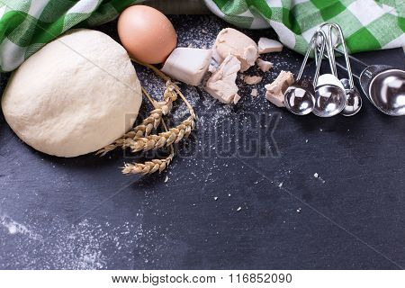 Dough And Ingredients For It - Eggs, Flour, Yeast On Dark Slate Background.