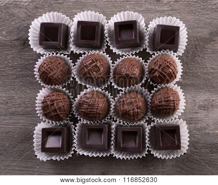 Assorted chocolate candies on wooden background