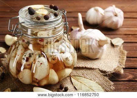 Canned garlic with spices on wooden background