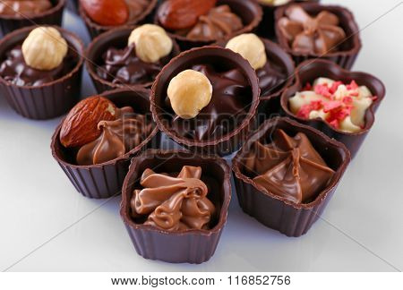 Delicious chocolate candies on white background, close up