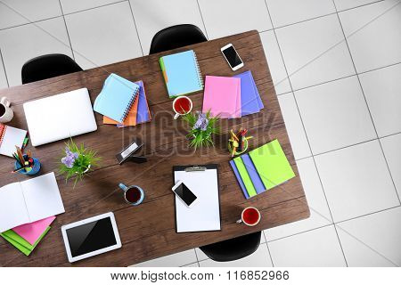 Session concept. Table with tablet, laptop, papers and cups of tea. Top view.