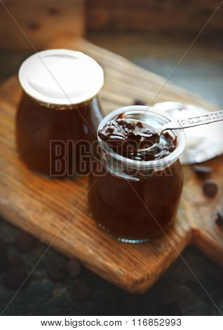 Chocolate dessert in a small glass jars on wooden background