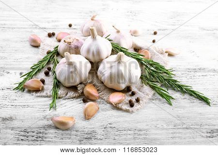 Composition of garlic and rosemary on wooden background