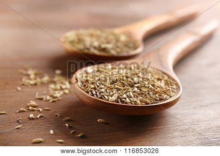 Two wooden spoons with cumin on the table, close-up