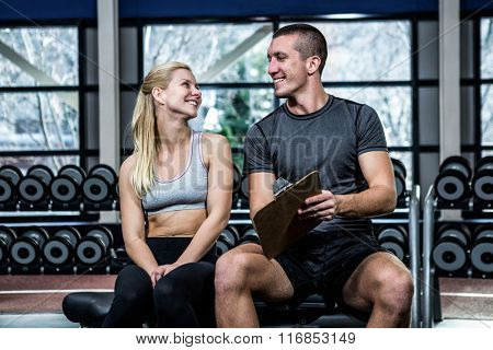 Fit woman discussing performance with trainer at gym