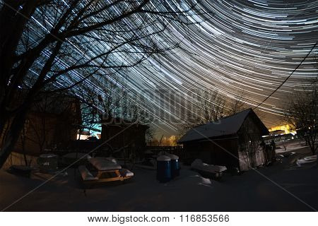 Winter garden with buildings and trees and starry sky with star trails