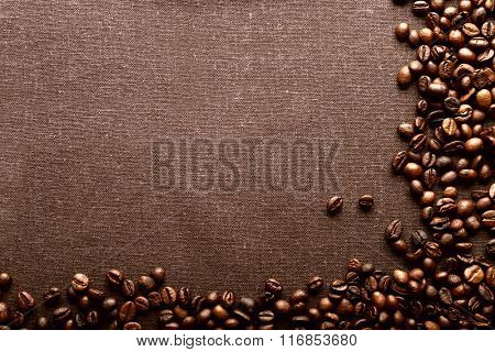 Roasted coffee beans on grey textile background