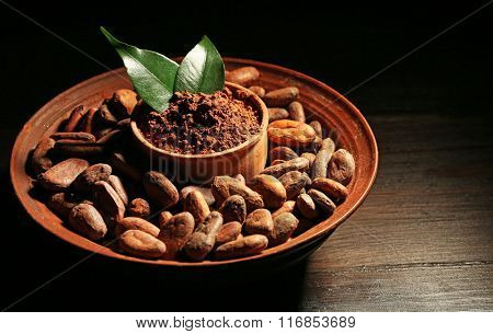 Bowl with aromatic cocoa harvest on wooden background, close up