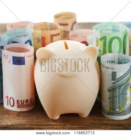 Piggy bank with rolled euro banknotes isolated on white