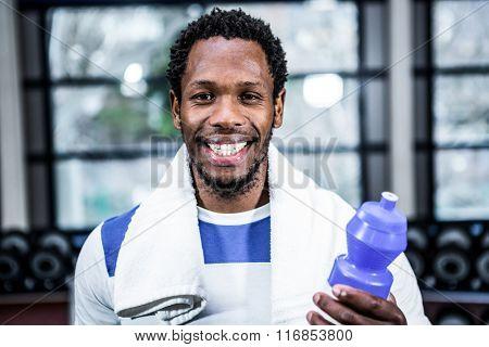 Smiling muscular man posing at gym