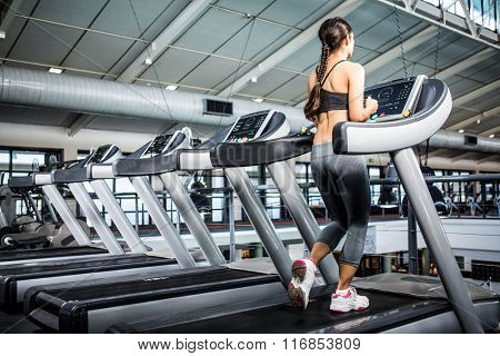 Rear view of woman jogging in treadmill at gym