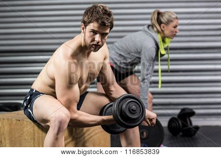 Man and woman lifting dumbbells at crossfit gym