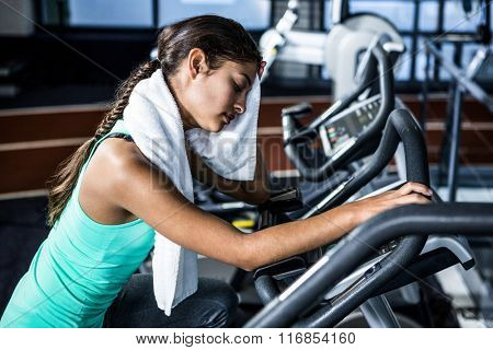 Tired fit woman wiping herself while doing bike exercising