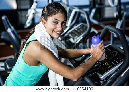 Smiling fit woman taking a break at gym