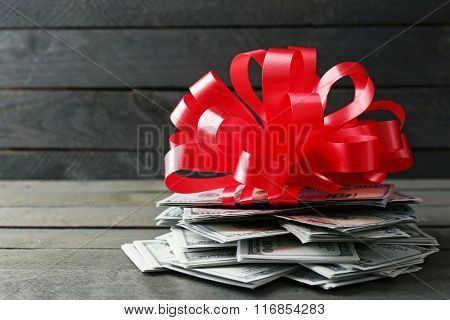 Pile of dollars with bow as gift on wooden background
