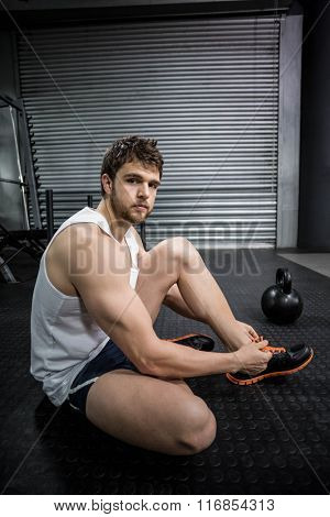 Fit man tying his shoelaces at crossfit gym