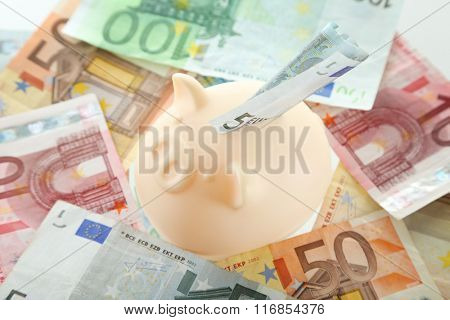 Piggy bank on pile of euro background