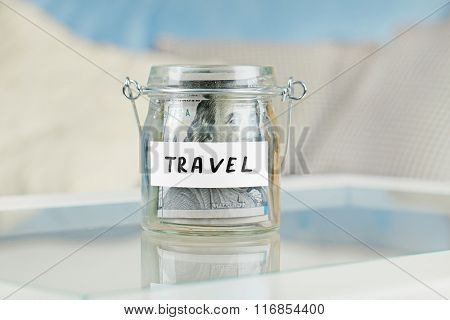 Glass jar with dollar banknotes for travel on a table