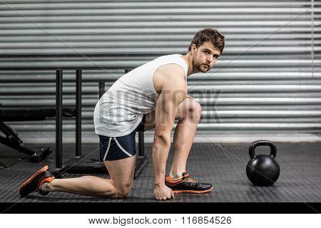 Serious fit man posing at crossfit gym