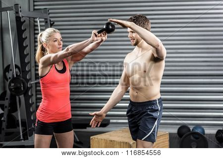 Couple exercising with dumbbells at crossfit gym