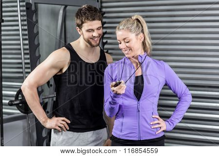 Female trainer showing timer at crossfit gym