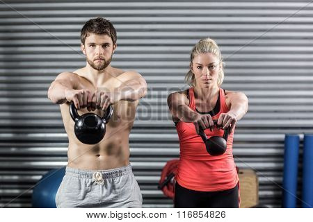 Couple lifting dumbbells together at crossfit gym