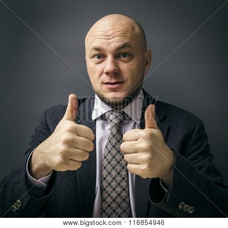 Portrait of an adult man in a business suit on a black background. Man giving thumbs up pointing fingers at camera