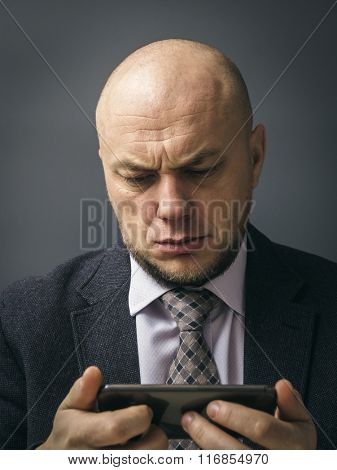 Portrait of an adult man in a business suit on a black background. Sad man almost in tears by what he sees on his cell phone, an sms, text message or email
