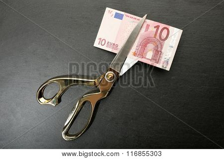 Golden scissors cut money on black background