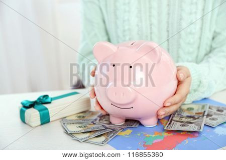Woman holding piggy bank with dollar banknotes. Savings money for gifts concept