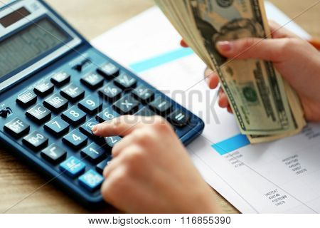 Woman counting money and working on calculator at the table
