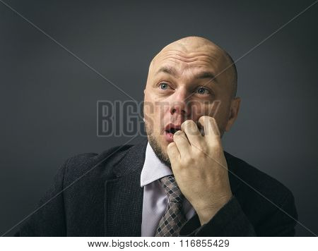 Portrait of an adult man in a business suit on a black background. Man looking surprised in full disbelief wide open mouth