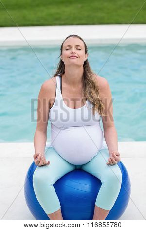 Pregnant woman sitting on exercise ball next to the pool