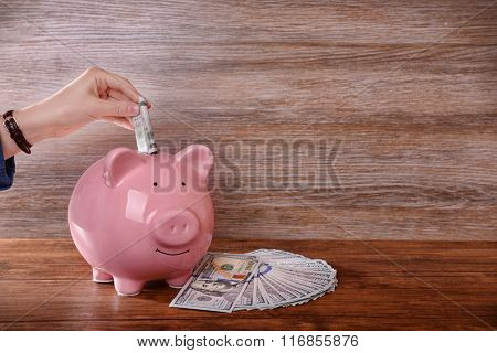 Woman putting dollar banknotes in pig moneybox