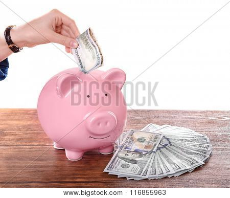 Woman putting dollar banknote in pig moneybox