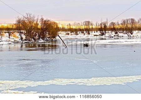 River with ice and snow-covered beach with trees