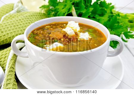 Soup lentil with spinach and cheese in white bowl on board
