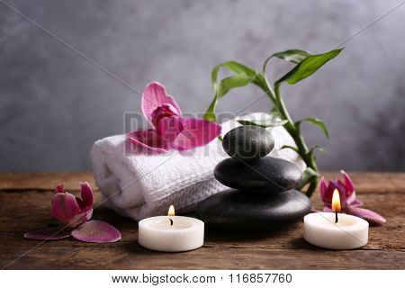 Spa stones with candles, purple orchid, bamboo and towel on wooden table against grey background