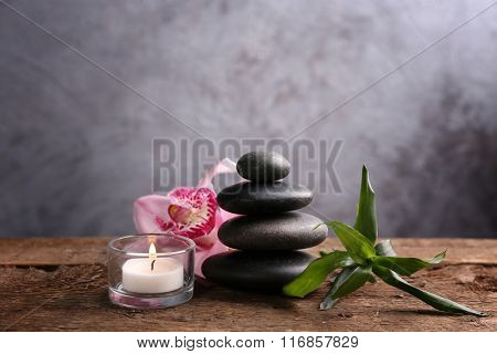 Spa stones with bamboo, pink orchid and candle on wooden table against grey background