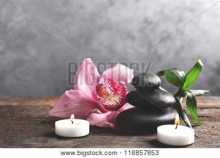 Spa stones with bamboo, pink orchid and candles on wooden table against grey background